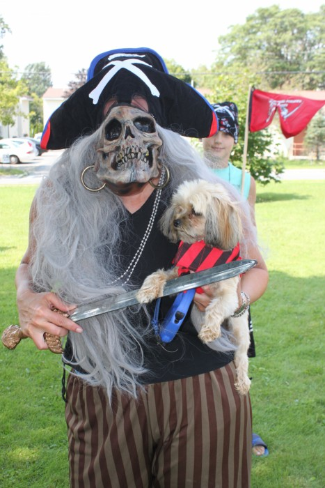 Person in pirate costume with skull mask holding a sword and a dog