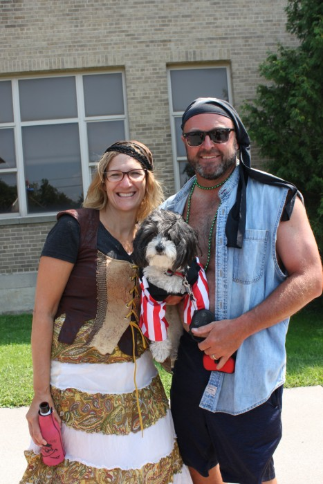 Man and woman in pirate costumes holding dog