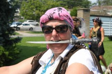 Woman in pirate costume with knife in mouth
