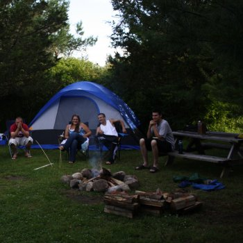 Group of tent campers around campfire at 1000 Islands Campground | Alexandria Bay, NY