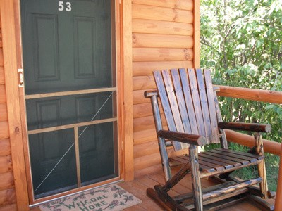 Log cabin with wooden rocking chair outside