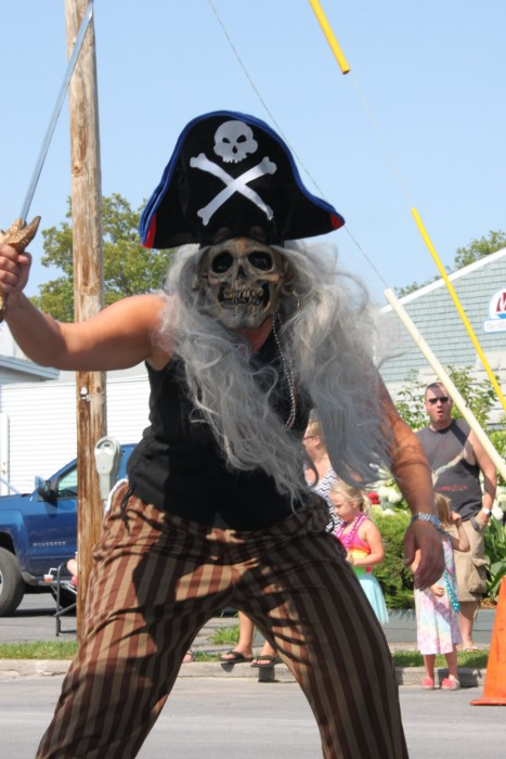 Person in pirate costume holding sword with skull mask