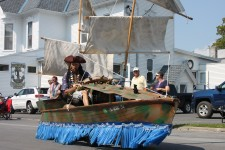Man in pirate costume driving boat in parade