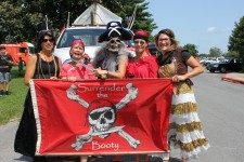 Several people in pirate costumes holding flag with skull and bones which reads Surrender the Booty