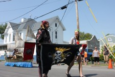 Two girls in parade carrying pirate banner